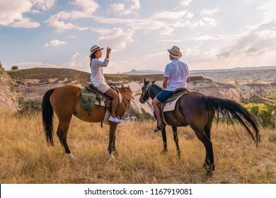 Horseback riding through the national Park in Cappadocia, Turkey, young woman and man couple riding horse at the mountains of Kapadokya