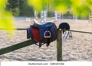Horseback saddle on the wooden fence in a sunny day