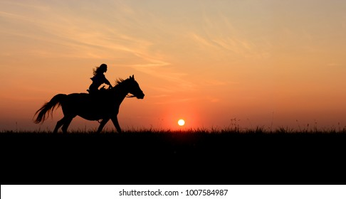 Horseback woman riding on galloping horse with red rising sun on horizon. Beautiful colorful sunset background with equine and girls silhouette.