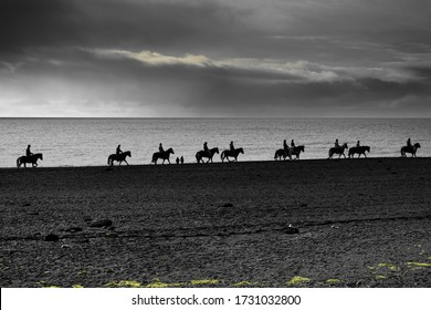 Horsebackriding on the beach in iceland on a cloudy day