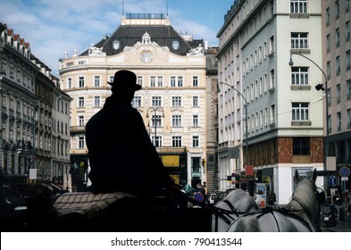 Horse-drawn carriage fiaker with silhouette of coachman as tourist guide walking along the ancient streets of Vienna, Austria