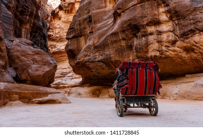 Horse-drawn carriage moving in the narrow canyon valley in the Ancient City. Petra's largest monument, UNESCO World Heritage Site, Jordan. The Siq, a narrow stone gallery