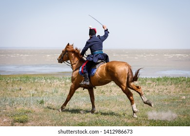 Horseman in blue military clothes riding along the seashore with a sabre in his hand