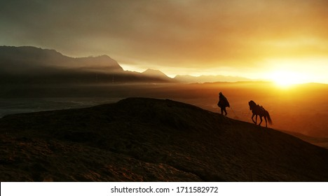 A horseman with his horse at a mountain during misty morning