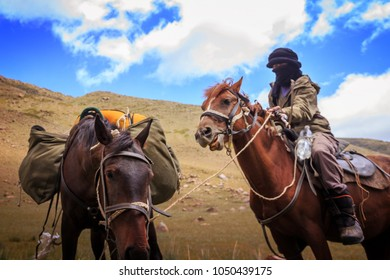 a horseman travelling on his horse in the wild mountain of Kyrgyzstan