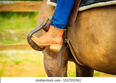 Horsemanship equipment concept. Closeup of woman foot in stirrup on horse saddle
