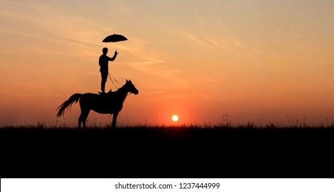 Horsemanship and trick-riding scene: men, standing on horse with open umbrella.  Romantic scene on idyllic sunset.
