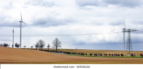 Horsemen in folk costumes among wind turbines and transmission lines