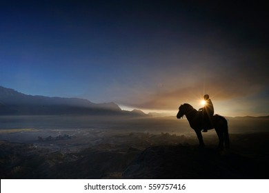 Horsemen with his horse on top of highland during sunrise