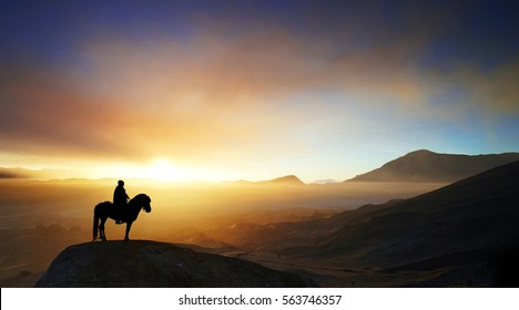 A horsemen riding his horse at top of hill during sunrise