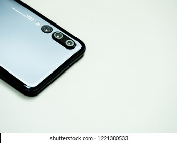 Horsens, Denmark - October 2018: Black Huawei p20 pro isolated on white background in upper left corner. Three cameras and Leica logo visible next to them. Shiny smart phone with great features.