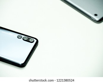 Horsens, Denmark - October 2018: Huawei p20 pro and Apple iPad Air isolated on white background. The LEICA logo is visible on the back of the black shiny smart phone.