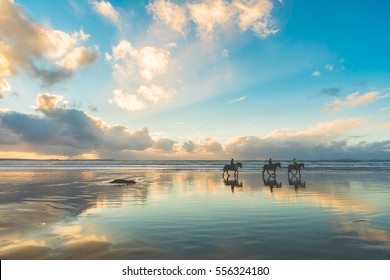 Horses walking on the beach at sunset. Three people riding horses at seaside on a cloudy day. Epic photo, wide angle shot, backlight with silhouette. Sport and travel concepts