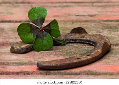 horseshoe and four leaf clover on wood
