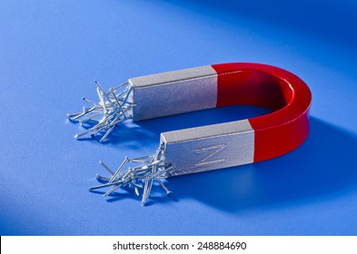 Horseshoe magnet holding a bunch of nails. Blue background.