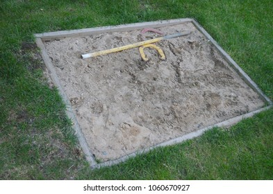 Horseshoe pit in backyard sandbox surrounded buy green grass during summer