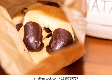 Horseshoes, typical Italian biscuits, in a paper bag resting on a wooden table.