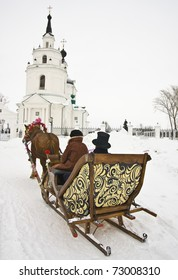 Horse-sleigh wagon driven by a coachman snow-covered road to the church.
