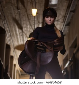 Horsewoman holding saddle at stable.Horse riding sport.