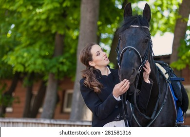 horsewoman jockey in uniform standing with black horse outdoors
