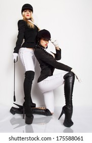 Horsewomans.Two attractive sexy girls posing in fetish outfits. Studio shot