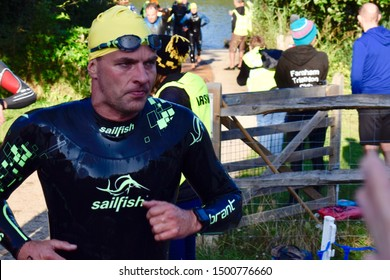 Horsham, UK - Sept 1 2019 - Triathlete making his way to transition in his Sailfish wetsuit following an open water swim