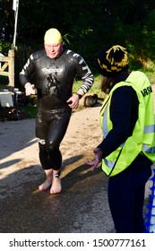 Horsham, UK - Sept 7 2019 - Triathlete making his way to transition in his Orca wetsuit following an open water swim