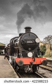 HORSTED KEYNES, UK - MARCH 19, 2016: Driver climbs into cabin of a steam engine on the Bluebell Line