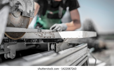 Horticulturist checks alignment with spirit level before cutting a large stone slab with the stone saw