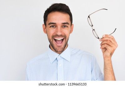 Horziontal closeup portrait of happy unshaven handsome young male with open wide mouth, wins the bad eyesight don't need glasses anymore, posing against white studio background. People, success