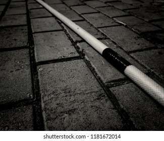 Hose on sidewalk. Pavement tiles. Hosepipe. Abstract. Black and white photo