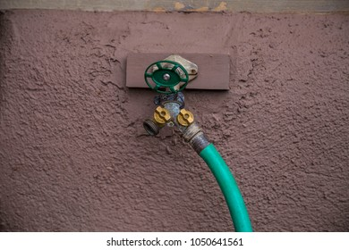 Hose valve close up green dial nozzle stucco wall screwed in spigot