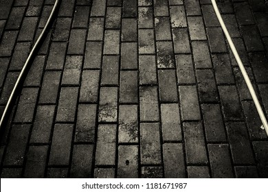 Hoses on sidewalk. Pavement tiles. Hosepipes. Abstract. Black and white photo. Grunge background