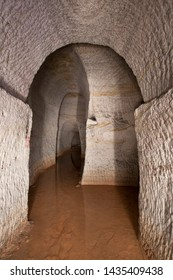 """Hosin, Czech republic - May 21 2011: Adit of an old kaolin mine named """"Orty"""". More corridors meet at this point, lower part of the mining drift is flooded by stall muddy water."""
