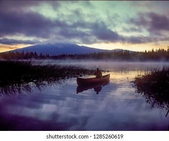 Hosmer Lake, Oregon - 8/16/2014:  A man paddling a Red canoe on Hosmer Lake with Mt Bachelor in the background, Oregon