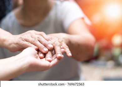 Hospice care community concept. Hands of elderly people and hand of caregiver support under in nursing home or wellbeing county.