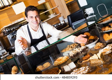 Hospitable man with delicious cream pies at bakery display