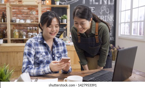 Hospitable waitress help to customer what to choose. smiling asian woman customer with friendly barista sharting cellphone screen menu taking order in cafe bar. lady in apron service in coffee shop.