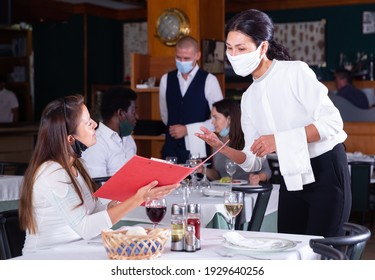 Hospitable waitress in protective mask helping attractive girl with menu, taking order in restaurant. Concept of restaurants reopening after quarantine