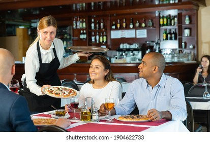 Hospitable young waitress bringing delicious pizzas to guests of cozy italian pizzeria