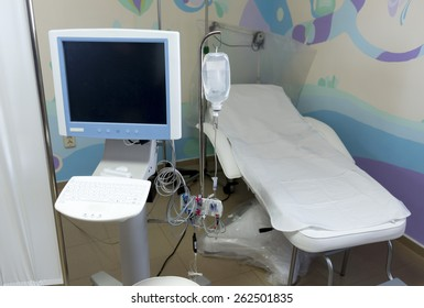 Hospital bed in a children's section with medical equipment.
