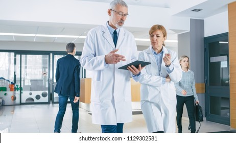 In the Hospital, Busy Doctors Talk, Using Tablet Computer While Walking Through the Building. New Modern Fully Functional Medical Facility.