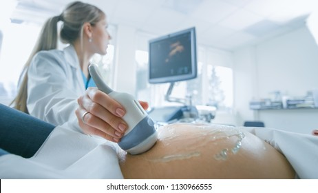 In the Hospital, Close-up Shot of the Doctor does Ultrasound / Sonogram Procedure to a Pregnant Woman. Obstetrician Moving Transducer on the Belly of the Future Mother.