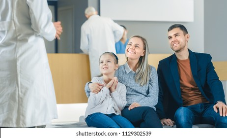 In the Hospital, Doctor Approaches Young Family of Father, Mother and Cute Little Daughter Sitting in the Lobby. The News are Good, Happy Moment in the Life of Young Family. Modern, Clean Hospital.