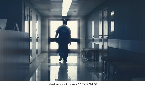 In the Hospital Elderly Pensioner Man Walks down the Hallway with Light in the End. Clean Modern Medical Facility. Life after Death, Door to Heaven Concept.
