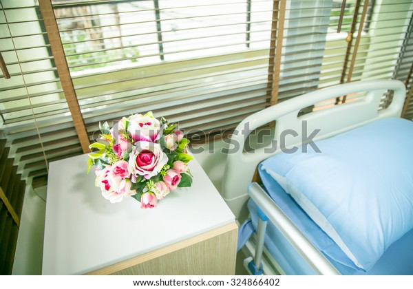 Hospital: Focus On Flowers Next To Hospital Bed