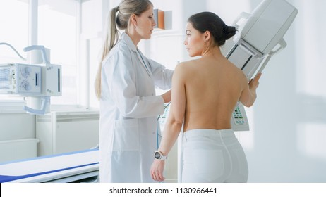 In the Hospital, Mammography Technologist / Doctor adjusts Mammogram Machine for a Female Patient. Friendly Doctor Explains Importance of Breast Cancer Prevention Screening. Modern Hospital.