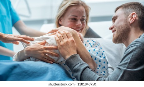 In the Hospital Midwife Gives Newborn Baby to a Mother to Hold, Supportive Father Lovingly Hugging Baby and Wife. Happy Family in the Modern Delivery Ward.