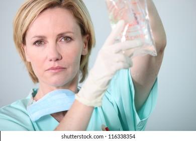 Hospital nurse attending to a drip bag