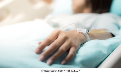 Hospital and patient concept -  Asian patient woman sleep in bed with iv solution on her hand in room of hospital